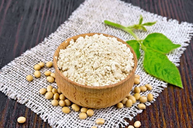 Soy flour in the bowl, soybeans on burlap, green leaf against the background of dark wooden boards