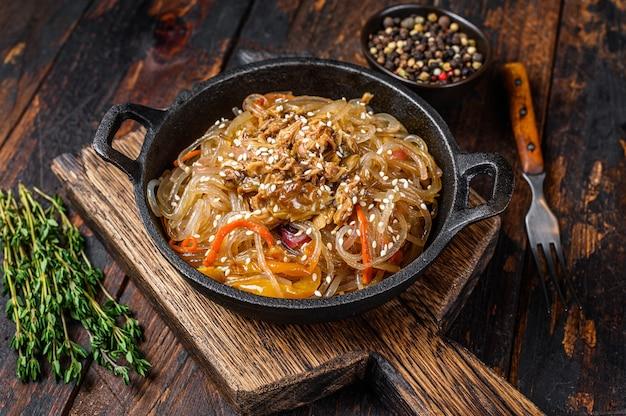 Лапша из соевого стекла с грибами шиитаке и куриным мясом. деревянный стол. вид сверху.