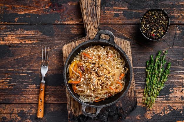 표고 버섯과 닭고기를 곁들인 간장 유리 국수. 나무 테이블. 평면도.