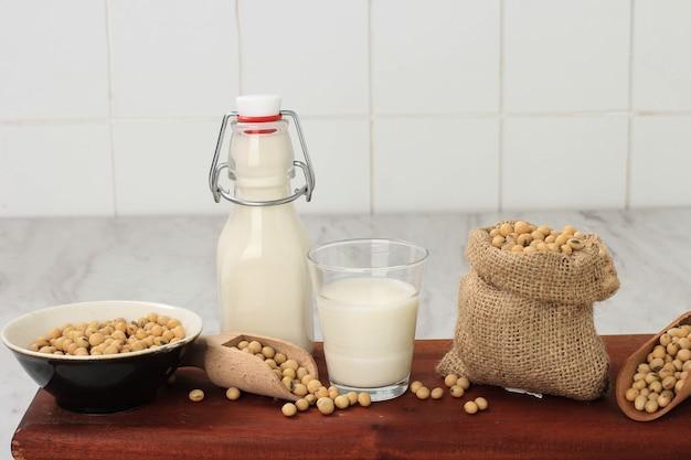 Соевое молоко и зерна на деревянном столе и фоне деревенской кухни. альтернативная концепция молока. передний план