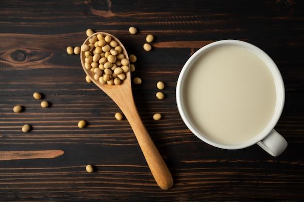 Соевое молоко и фасоль сои на деревянном столе.