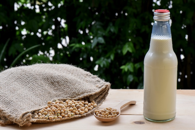 Soy milk in bottles and soy on a spoon poured out from the hemp sack bag on the wooden floor