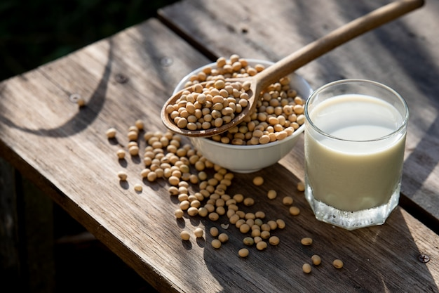 Soy milk cool and soybeans on wooden table  with lighting in the morning