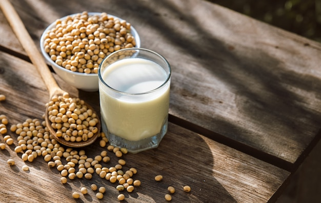 Soy milk cool and soybeans on wooden table
