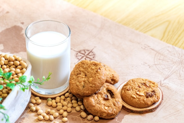 Soy milk in glass and cookie with soy bean on bucket at morning time. nature healthy concept.