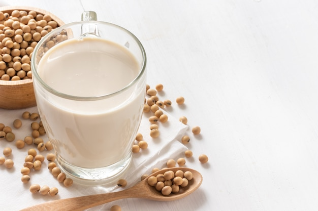 Soy milk in a glass with soybeans in wooden bowl