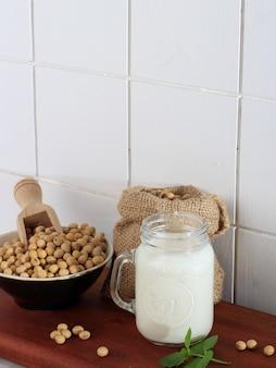 Соевое молоко в банке для напитков и соевые бобы в миске. здоровая концепция немолочного молока