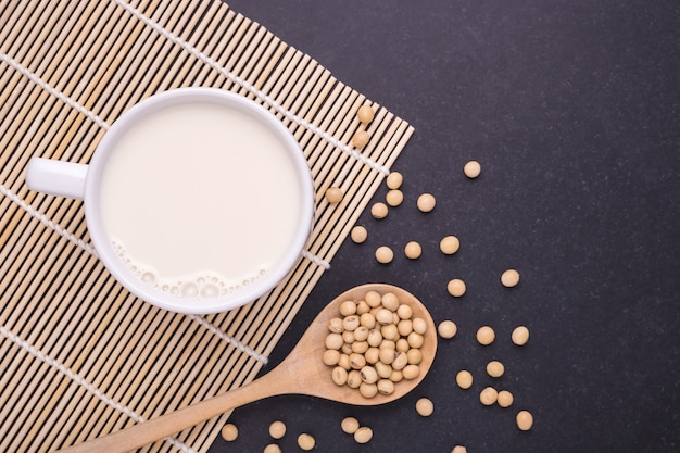 Soy milk in white cup and soy bean on dark table background. top view