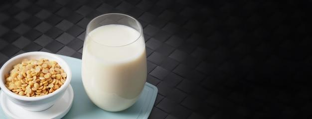 Соевое молоко без сахара в стакане на зеленом пластиковом коврике крупным планом изображения