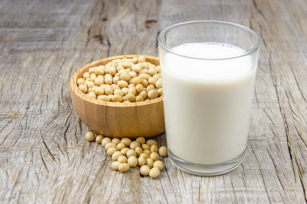 Soy milk with soybean on wooden background.