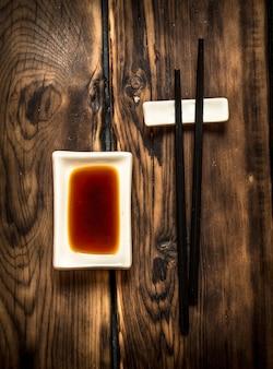 Соевый соус и палочки для суши. на деревянном фоне.