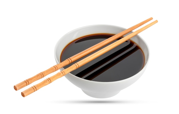 Соевый соус и палочки для еды, изолированные на белом фоне, с обтравочным контуром