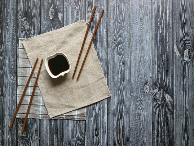 Soy sauce and chopsticks on a dark wooden table with copy space.