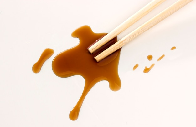 Soy sauce and chopsticks on white surface