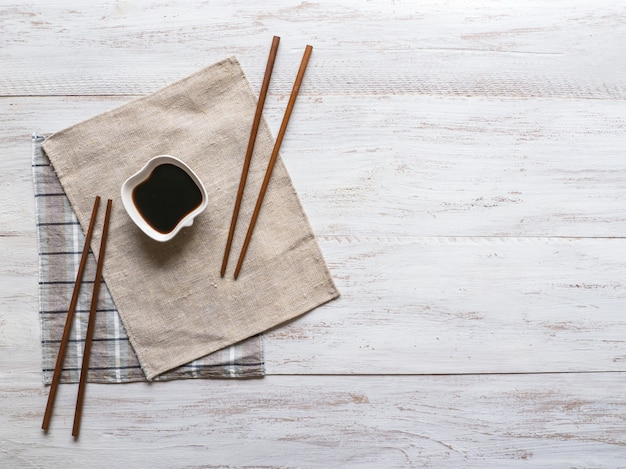 Soy sauce and chopsticks on a white wooden background