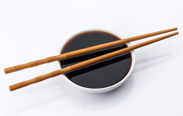 Soy sauce and chopsticks on white