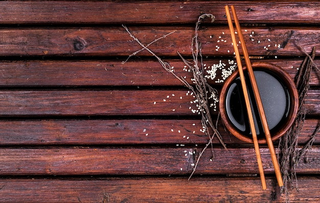Soy sauce and chopsticks on wooden table