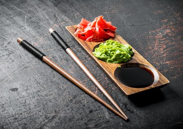 Соевый соус, имбирь и васаби на деревянной подставке с палочками для еды. на темном деревенском фоне