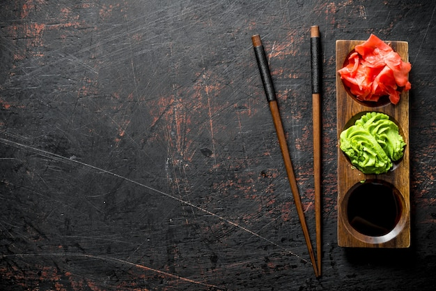 Soy sauce, ginger and wasabi on a wooden stand with chopsticks. on dark rustic