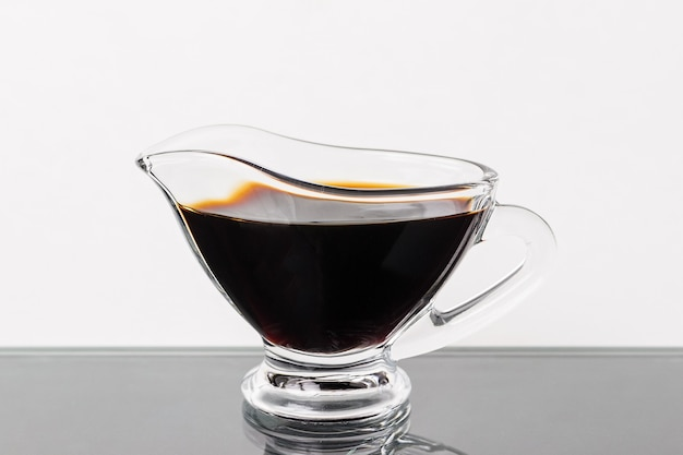 Soy sauce in a glass gravy boat on a black table
