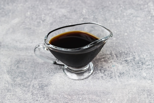 Soy sauce in a glass gravy boat on a grey table. dish of soy sauce on grey table.