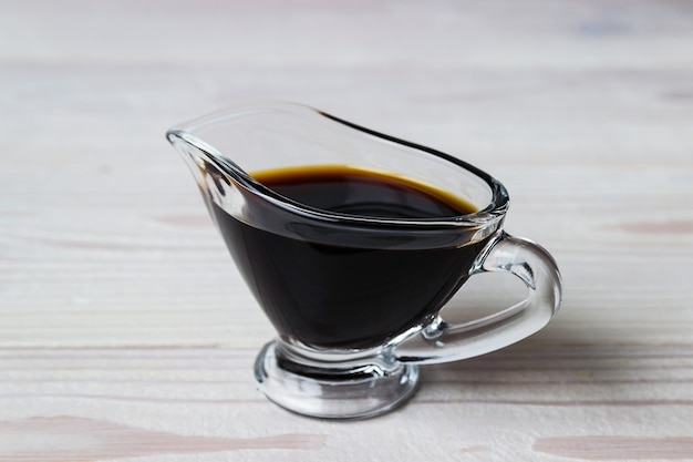 Soy sauce in a glass gravy boat on a white wooden surface