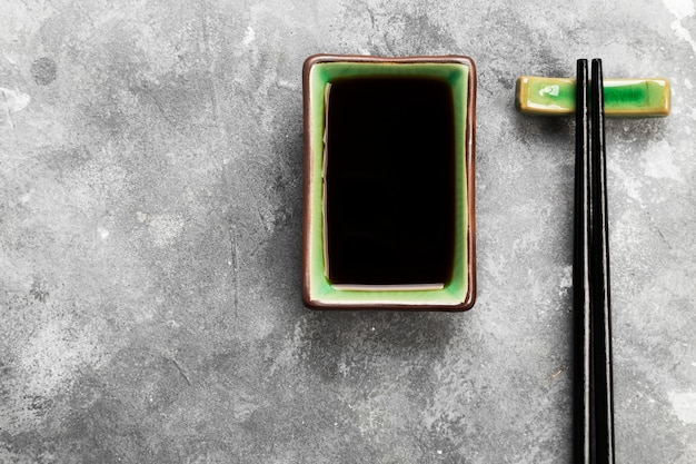 Соевый соус в традиционной азиатской посуде на сером фоне. вид сверху, скопируйте пространство. пищевой фон