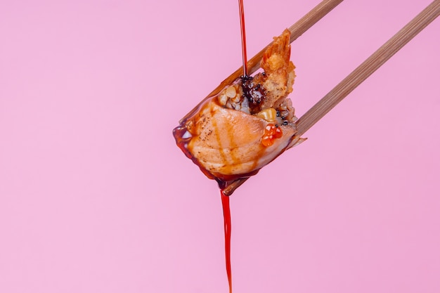 Soy sauce pouring on a roll on pink background