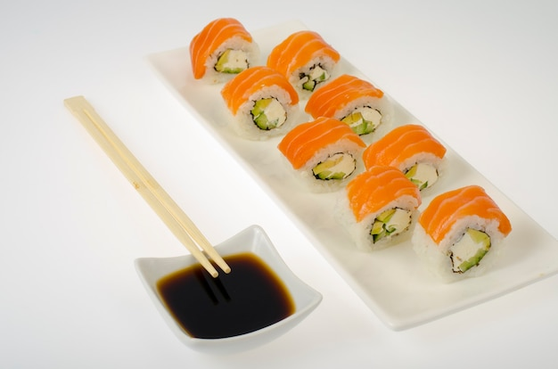 Soy sauce and rolls with salmon on white background. studio photo