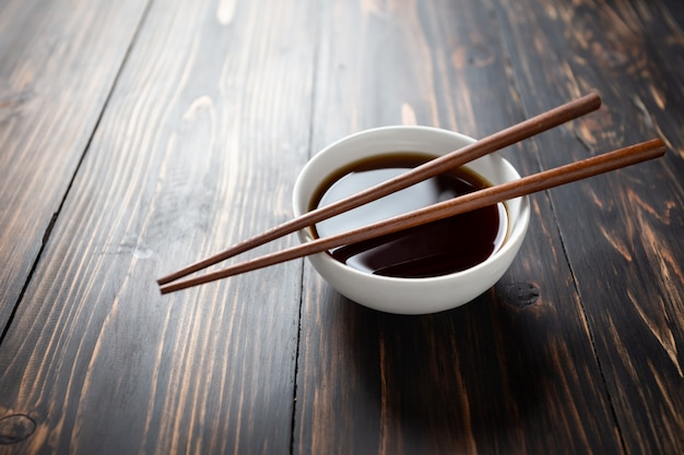 Soy sauce and soy bean on wooden table.