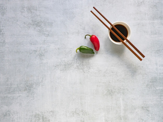 Soy sauce with chopsticks and hot pepper on the table. copy space.