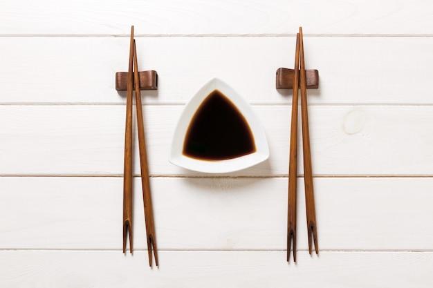Соевый соус с палочками на белом фоне деревянный стол