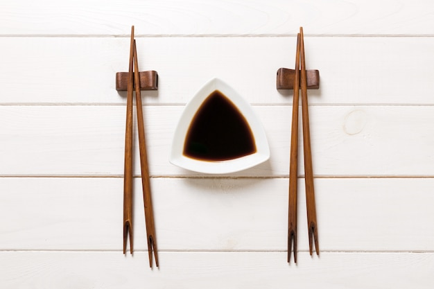 Soy sauce with chopsticks on white wooden table background