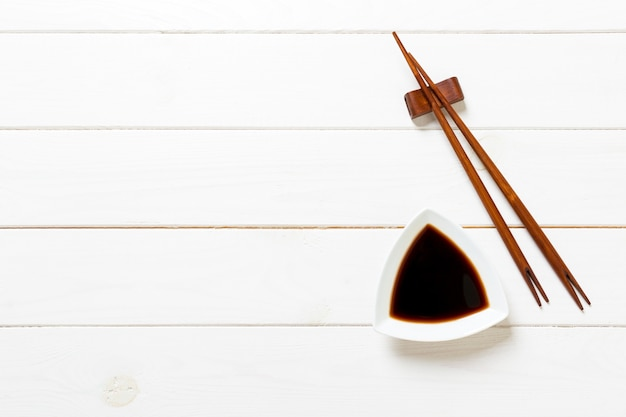 Soy sauce with chopsticks on white wooden table
