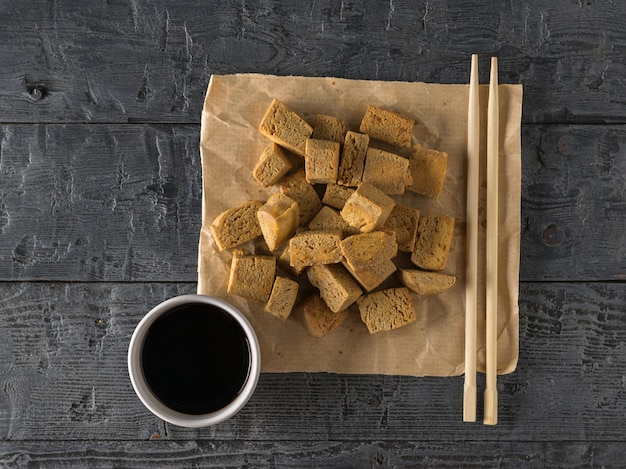 Соевый соус с жареным тофу и деревянными палочками. закуска с сыром на гриле.