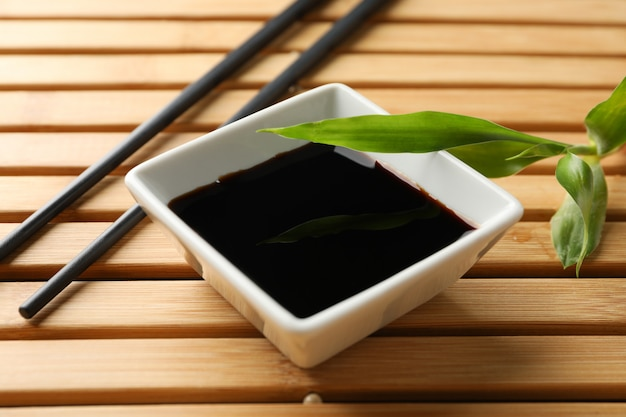Soy sauce on wooden background, space for text. closeup