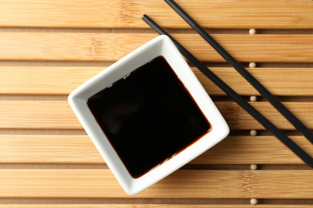 Soy sauce on wooden background, space for text. top view