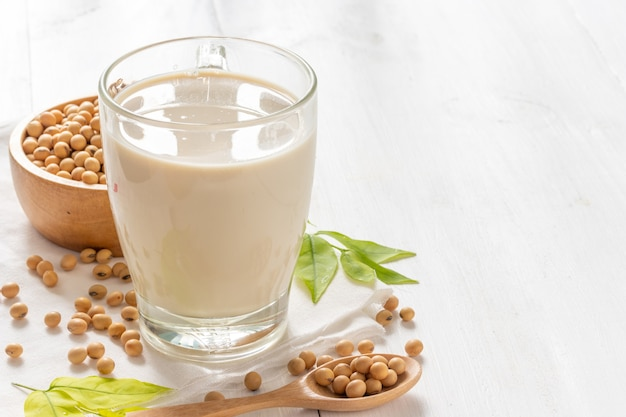 Soy or soya milk in a glass with soybeans in wooden bowl background