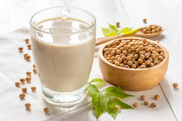 Soy or soya milk in a glass with soybeans in wooden bowl