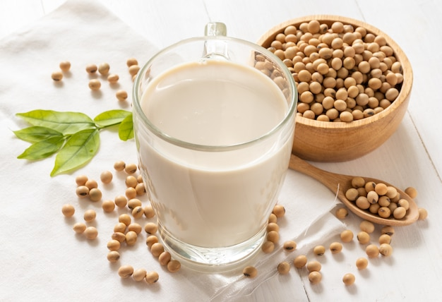 Soy or soymilk in glass with soybeans in wooden bowl