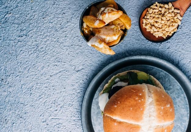 블루 테이블 배경에 금속 그릇에 향신료와 소스와 감자 튀김 간장 채식 버거