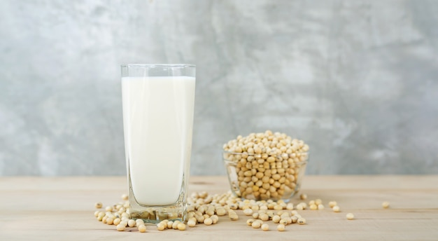 Soybean in a bowl and soy milk on a wooden background.