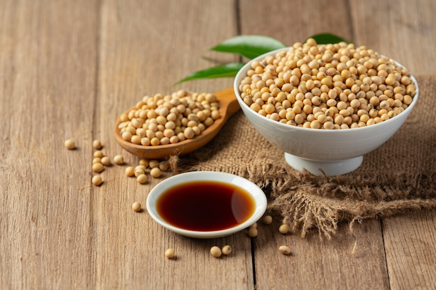 Soybean sauce and soybean on wooden floor soy sauce food nutrition concept.