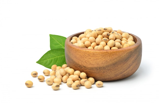 Soybean seeds in wooden bowl with green leaves isolated on white.