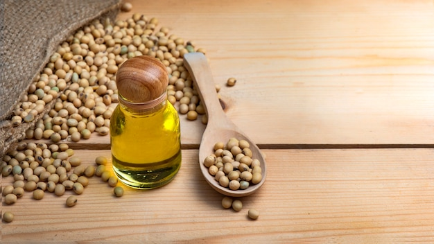 Soybean and soybean oil are in a sack bag. placed on a wooden table