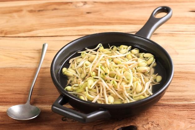 Суп из ростков соевых бобов с рисом (kongnamul gukbap), освежающий в корейском стиле, подается на белой миске, на черном деревянном столе с нарезанным зеленым луком сверху.