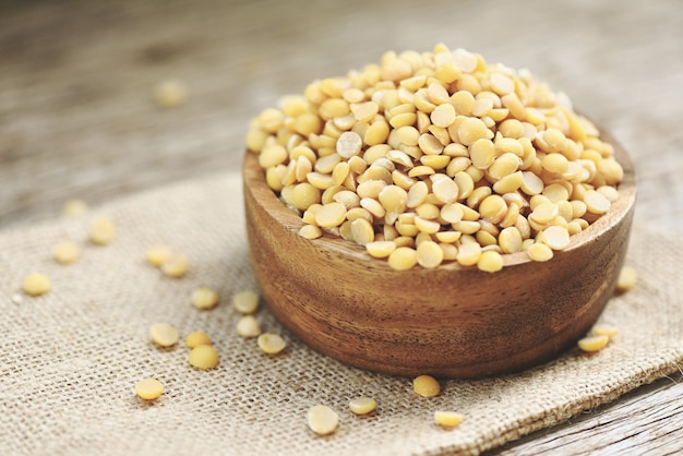 Soybean in a wooden bowl agricultural products on the sack background - peeled split soybean or soya bean without husk