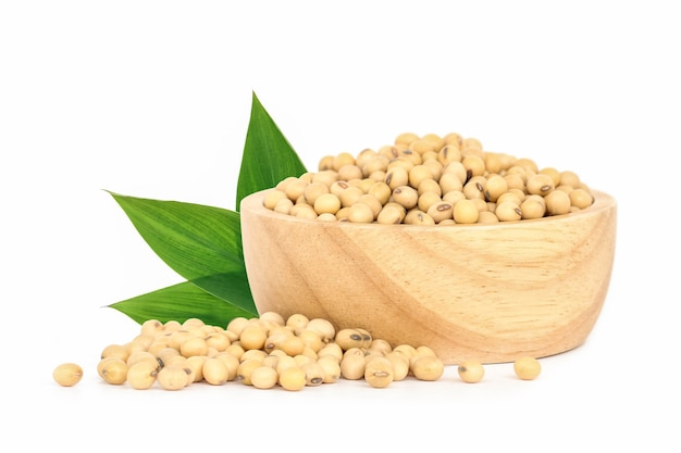 Soybean in wooden bowl with green leaves isolated on white background.