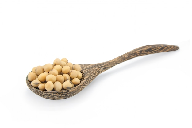 Soybean on wooden spoon isolated on white with clipping path.