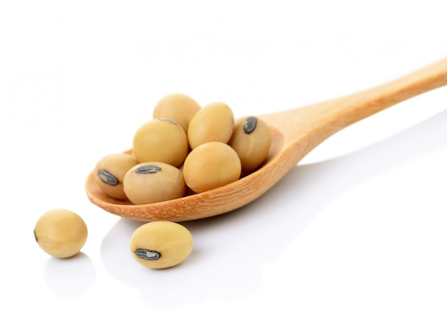 Soybean in wooden spoon on white space